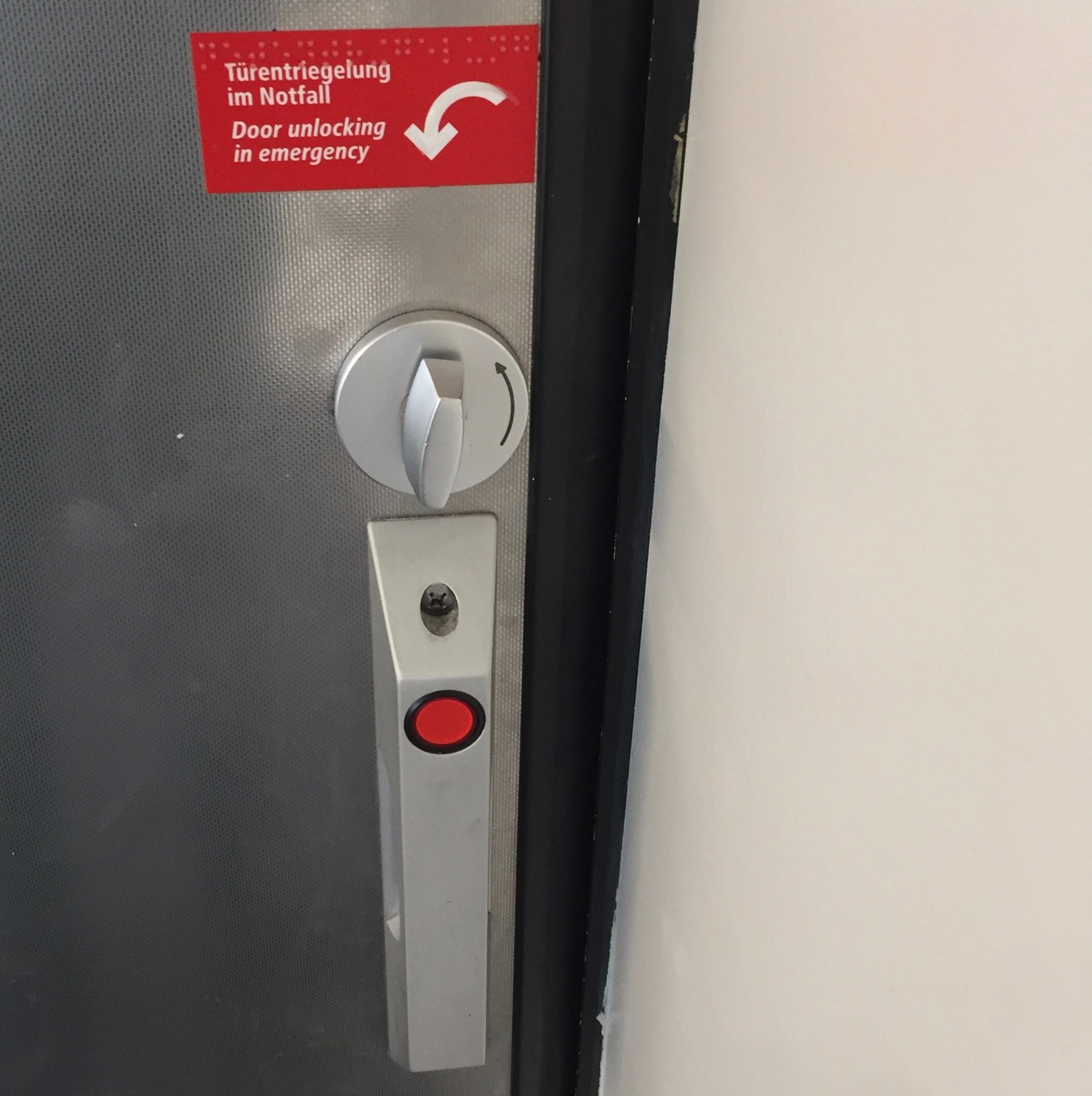 "The inside of the toilet door, a similar door handle as before is visible. But this time the red circle is at the top, and there is no green area for opening or closing. There is only a weird mechanical dial above the handle. And above that dial is a white note on red ground that says ""Door unlocking emergency"", next to an arrow indicating that dial must be turned counter-clockwise."